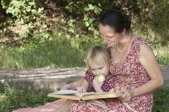 A menina mastiga a maçã, olhando o livro Imagens de Stock Royalty Free