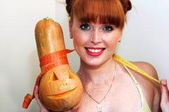 A menina mede uma abóbora Foto de Stock Royalty Free