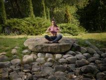 A menina meditates na posição de lótus Imagem de Stock