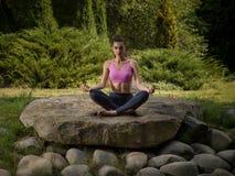 A menina meditates na posição de lótus Fotografia de Stock Royalty Free