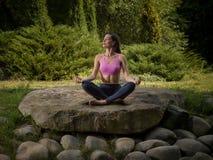 A menina meditates na posição de lótus Fotos de Stock Royalty Free