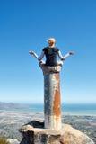 A menina meditates sobre a coluna nas montanhas imagem de stock