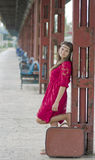 Menina meditativo com a mala de viagem que espera no estação de caminhos-de-ferro Fotografia de Stock