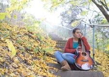 Menina meditativo com sua guitarra no outono Imagem de Stock Royalty Free