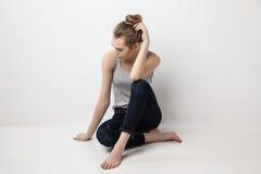 Menina melancólica bonita que senta-se no assoalho Imagens de Stock Royalty Free