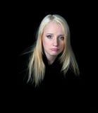 A menina melancólica em um fundo preto. Fotos de Stock