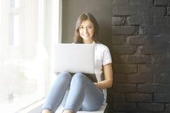 Menina milenar feliz com o portátil na soleira Retrato da jovem mulher com diferença do diastema entre os dentes Sorriso bonito i Imagens de Stock Royalty Free