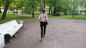 A menina modelo à moda elegante nos saltos altos anda no parque do verão filme