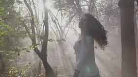 Menina modelo alegre nova que gira e que levanta em uma luz solar brilhante na floresta entre as folhas e o fumo de queda de outo vídeos de arquivo