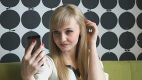 Menina modelo atrativa que faz selfies no café filme