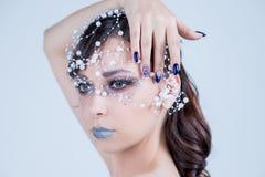 Menina modelo bonita com projeto azul, cara e cabelo do prego do tratamento de mãos com grânulos, cristais de rocha, decoração Co fotos de stock royalty free