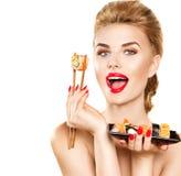 Menina modelo da beleza que come rolos de sushi imagem de stock