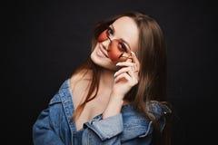 Menina modelo elegante e 'sexy' em óculos de sol à moda e no revestimento de calças de ganga com ombros despidos que sorri e que  fotos de stock