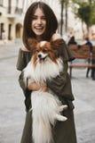 Menina modelo moreno bonita e alegre com sorriso brilhante, no vestido curto com um cão bonito pequeno do papillon em suas mãos q imagem de stock royalty free
