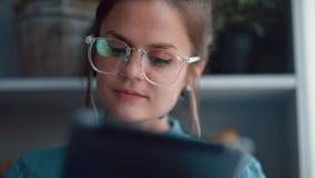 A menina moderna com uma tabuleta lê um livro ou comunica-se no Internet filme