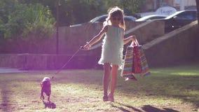 Menina moderna da forma que anda com o cão na trela após a compra com pacotes à disposição fora nos raios de sol filme