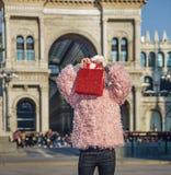 Menina moderna em Milão, Itália que esconde atrás do saco de compras vermelho Fotografia de Stock Royalty Free
