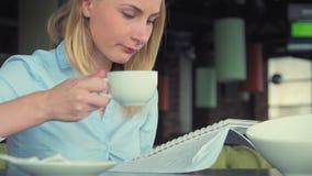 A menina moderna em um chá bebendo do café, usos a tabuleta e escreve no caderno Menina bonita no funcionamento da cafetaria ou filme
