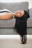 Menina feliz que coloca no sofá na sala de visitas Fotografia de Stock Royalty Free