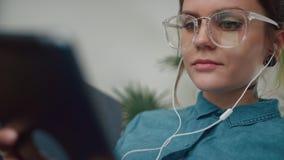 A menina moderna nova escuta a música, sorrisos, olhares na tela da tabuleta video estoque