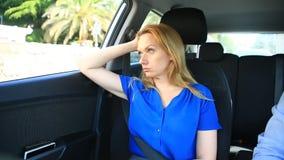 A menina monta no carro ao lado do motorista e dos olhares tristes para fora a janela video estoque