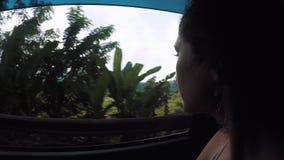 A menina monta no carro e olha para fora a janela em terraços do arroz e o vulcão Agung nas nuvens video estoque