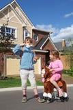 A menina monta no cavalo do brinquedo e o menino come doces de algodão Imagens de Stock Royalty Free