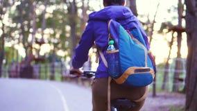 A menina monta no parque em uma bicicleta mo lento video estoque