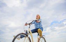 A menina monta o fundo do céu da bicicleta A mulher sente livre quando aprecie dar um ciclo O ciclismo dá-lhe o sentimento da lib fotografia de stock royalty free