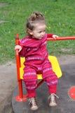 A menina monta um carrossel playground foto de stock