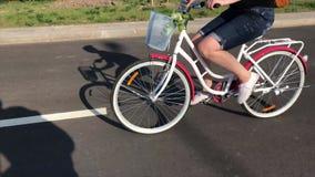 A menina monta uma bicicleta em uma estrada asfaltada Atr?s de sua trouxa, em uma cesta da carga um o grupo de flores video estoque