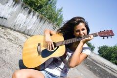 A menina morde a guitarra imagens de stock