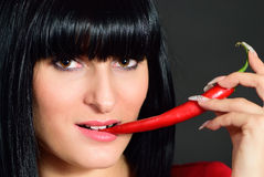 A menina morde a pimenta quente Imagem de Stock Royalty Free