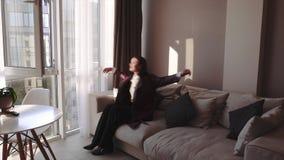 Menina moreno à moda adorável em seus apartamentos, olhando à janela com uma vista bonita e uma queda no divã macio vídeos de arquivo