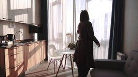 A menina moreno à moda adorável que vem a seus apartamentos novos, passando o corredor e vem à janela com um bonito video estoque