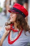 A menina moreno à moda vestida em uma blusa listrada, em uns grânulos vermelhos e em um tampão vermelho levanta na rua da cidade  imagens de stock