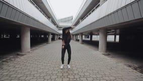 A menina moreno é de dança e de execução a dança moderna do hip-hop no estacionamento, estilo livre em industrial filme