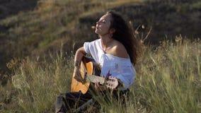 Menina moreno aciganada encaracolado que joga a guitarra e que canta no campo na inclinação do golfo vídeos de arquivo