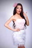 Menina moreno alegre bonita em um vestido cor-de-rosa e em uma coroa cor-de-rosa em sua cabeça Fotos de Stock