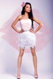 Menina moreno alegre bonita em um vestido cor-de-rosa e em uma coroa cor-de-rosa em sua cabeça Fotografia de Stock