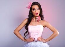 Menina moreno alegre bonita em um vestido cor-de-rosa e em uma coroa cor-de-rosa em sua cabeça Foto de Stock