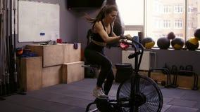 Menina moreno atrativa com o sportswear vestindo do dryfit do corpo desportivo que dá certo na bicicleta estacionária Aptidão e vídeos de arquivo