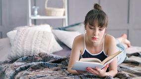 Menina moreno atrativa do tiro completo que encontra-se no estômago que cruza os pés desencapados no livro da cama e de leitura filme