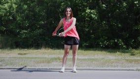 Menina moreno atrativa na dança cor-de-rosa da criança da trouxa da dança da camisa no parque Jovem mulher nos fones de ouvido qu vídeos de arquivo