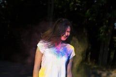 Menina moreno atrativa que levanta com explosão do pó de Gulal em t Fotografia de Stock Royalty Free