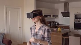 Menina moreno atrativa que usa seus auriculares do telefone VR em casa Vidros da realidade virtual na ação tiro do steadicam 4K vídeos de arquivo