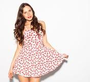 Menina moreno bonita com cabelo longo e os olhos azuis que levantam no vestido curto do verão em um fundo branco indoor foto de stock royalty free