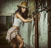 A menina moreno bonita com olhar do país, disparou dentro no estilo estável, rústico Mulher atrativa com chapéu de vaqueiro, shor Imagem de Stock