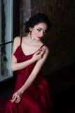 Menina moreno bonita com olhar sensual e mãos bonitas Retrato pela janela Imagem de Stock Royalty Free