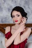 A menina moreno bonita com olhar sensual senta-se em um sofá leve Retrato Imagem de Stock